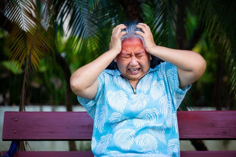 Ανώτερος γυναίκα αγγίζει το κεφάλι της όταν αισθάνεται πονοκέφαλο στοκ φωτογραφίες