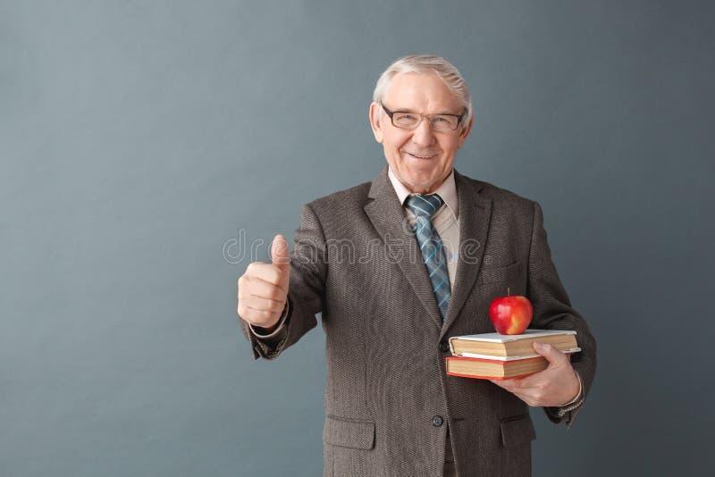 Ανώτερος δάσκαλος ατόμων που φορά τη στάση στούντιο γυαλιών που απομονώνεται σε γκρίζο με τα βιβλία και το μήλο που ανατρέχει χαρ στοκ εικόνα