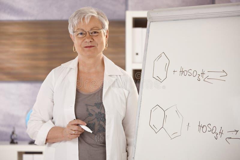 Ανώτερος δάσκαλος που εξηγεί τους μοριακούς τύπους στοκ εικόνες