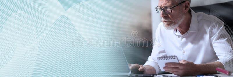 Ανώτερος επιχειρηματίας που εργάζεται στο lap-top, ελαφριά επίδραση, σκληρό φως έμβλημα πανοραμικό στοκ φωτογραφία με δικαίωμα ελεύθερης χρήσης