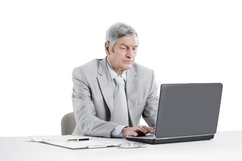Ανώτερος επιχειρηματίας που εργάζεται στο lap-top καθμένος στο γραφείο του στοκ φωτογραφία με δικαίωμα ελεύθερης χρήσης