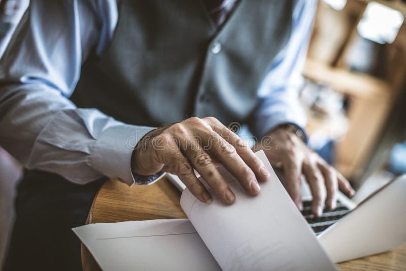Ανώτερος επιχειρηματίας που εργάζεται στο lap-top μαύρο στενό μαλακό επάνω λευκό μαξιλαριών μικροφώνων ακουστικών απομονωμένο εικ στοκ φωτογραφία