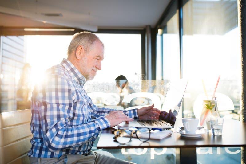 Ανώτερος επιχειρηματίας που εργάζεται στο lap-top στον καφέ στοκ φωτογραφία με δικαίωμα ελεύθερης χρήσης
