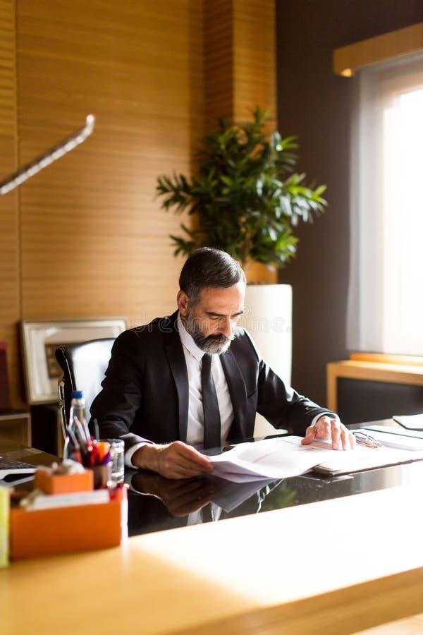 Ανώτερος επιχειρηματίας που εργάζεται στο lap-top στο σύγχρονο γραφείο στοκ εικόνα