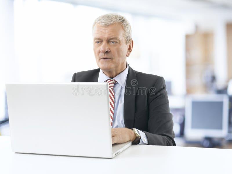 Ανώτερος επιχειρηματίας που εργάζεται στο lap-top στοκ φωτογραφίες