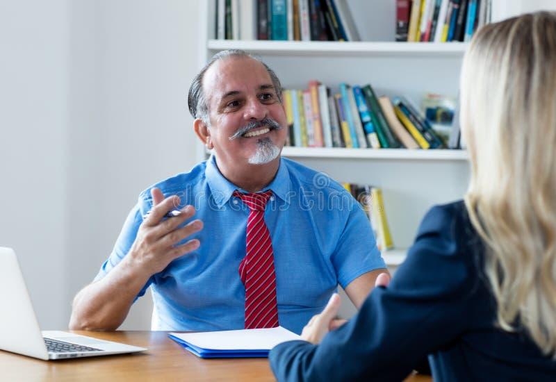Ανώτερος επιχειρηματίας που μιλά με τον υπάλληλο στοκ εικόνα