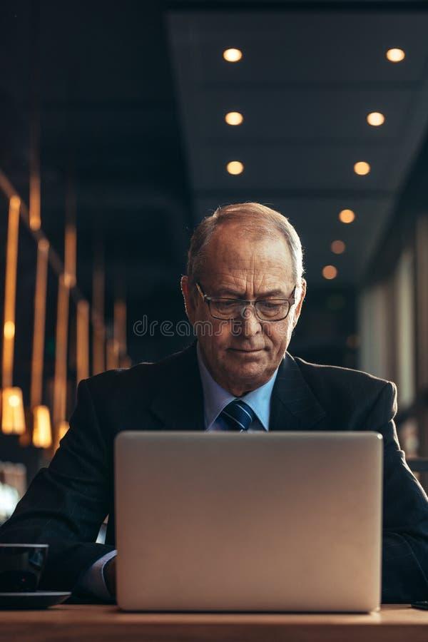 Ανώτερος επιχειρηματίας στον καφέ που λειτουργεί στο lap-top στοκ φωτογραφία με δικαίωμα ελεύθερης χρήσης