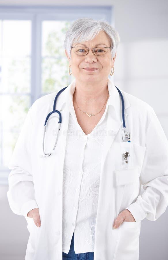 Ανώτερος θηλυκός γιατρός που χαμογελά στο διάδρομο νοσοκομείων στοκ φωτογραφίες