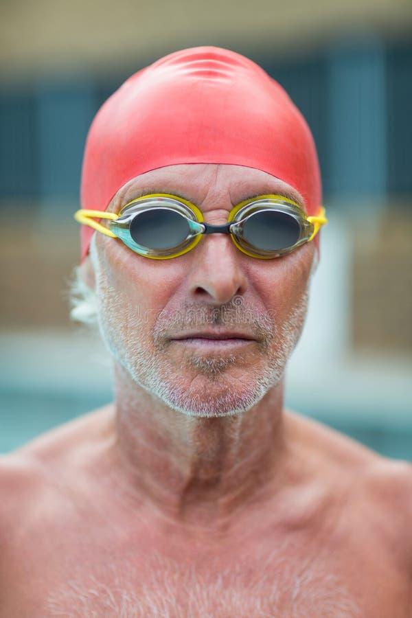 Ανώτερος κολυμβητής γυμνοστήθων που φορά τα προστατευτικά δίοπτρα στοκ εικόνες