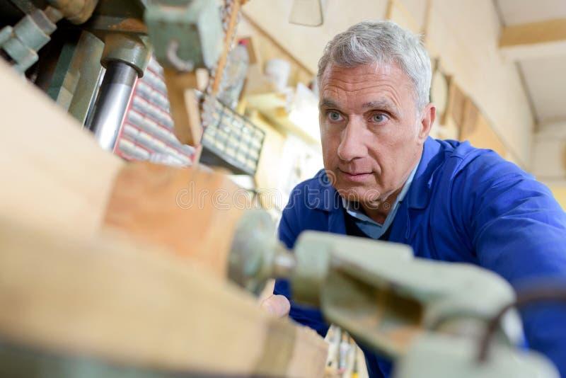 Ανώτερος ξυλουργός που εργάζεται στο εργαστήριο στοκ εικόνες