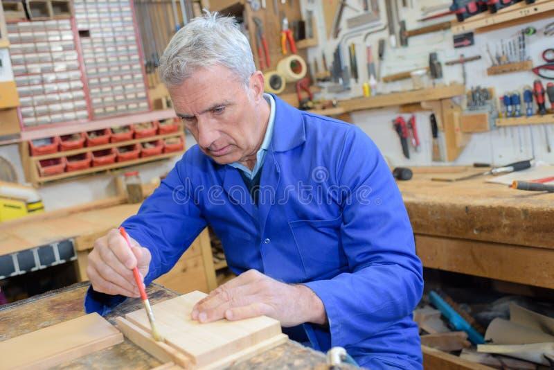 Ανώτερος ξυλουργός που χρησιμοποιεί τη βούρτσα στο ξύλο κομματιού στο εργαστήριο στοκ φωτογραφία