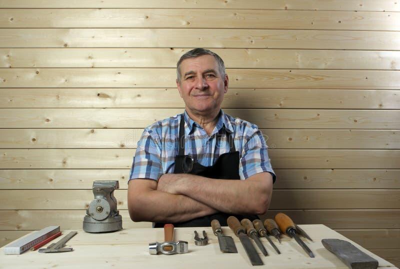Ανώτερος ξυλουργός που εργάζεται στο εργαστήριό του στοκ εικόνες
