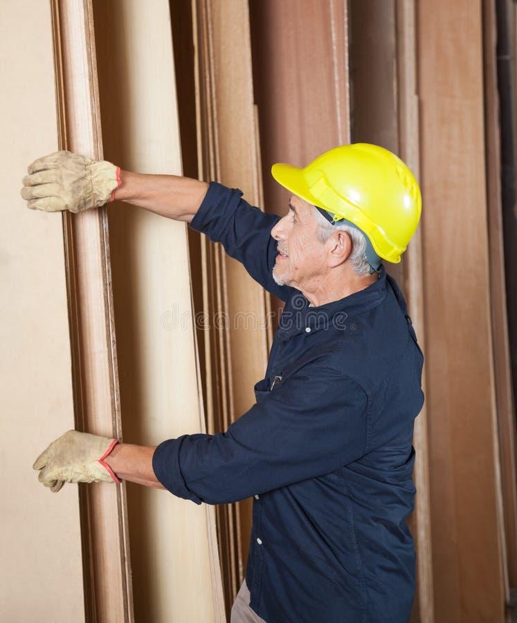 Ανώτερος ξυλουργός που τακτοποιεί τις σανίδες στο εργαστήριο στοκ εικόνες
