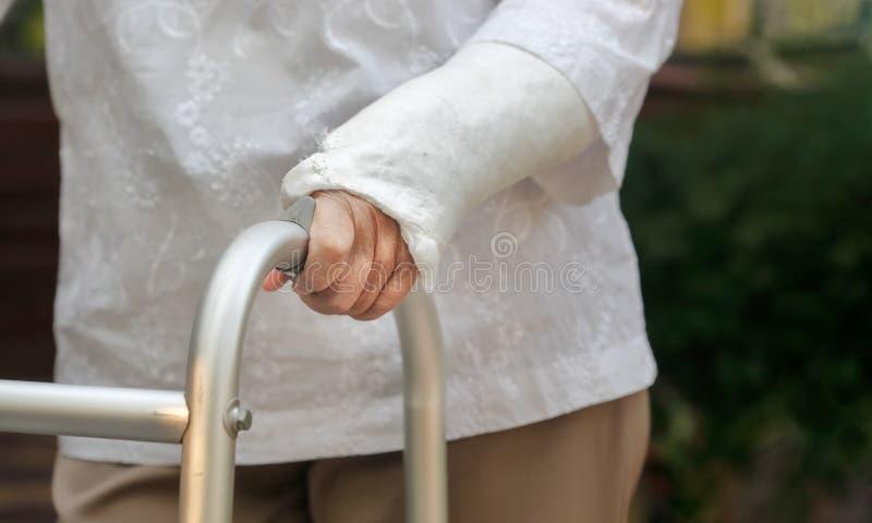 Ανώτερος σπασμένος γυναίκα καρπός που χρησιμοποιεί τον περιπατητή στο κατώφλι στοκ φωτογραφία