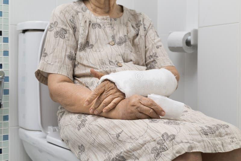 Ανώτερος σπασμένος γυναίκες καρπός που χρησιμοποιεί την τουαλέτα στοκ εικόνες με δικαίωμα ελεύθερης χρήσης