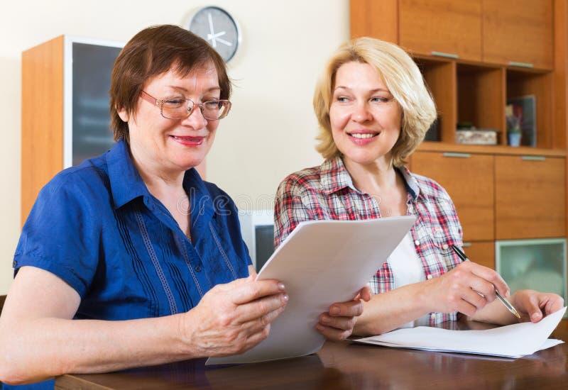 Ανώτερος υπάλληλος συμβολαιογράφων που βοηθά τον ηλικίας πελάτη στοκ φωτογραφίες