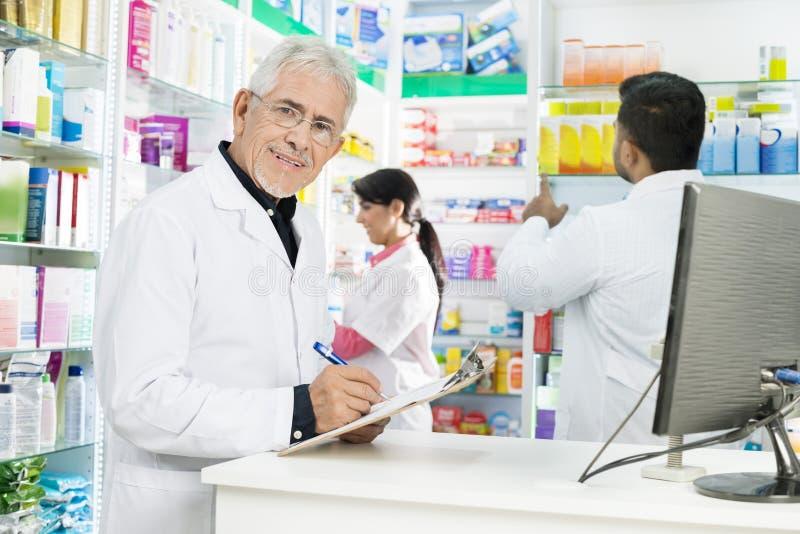 Ανώτερος φαρμακοποιός που γράφει στην περιοχή αποκομμάτων ενώ συνάδελφοι που εργάζονται στο Π στοκ εικόνα