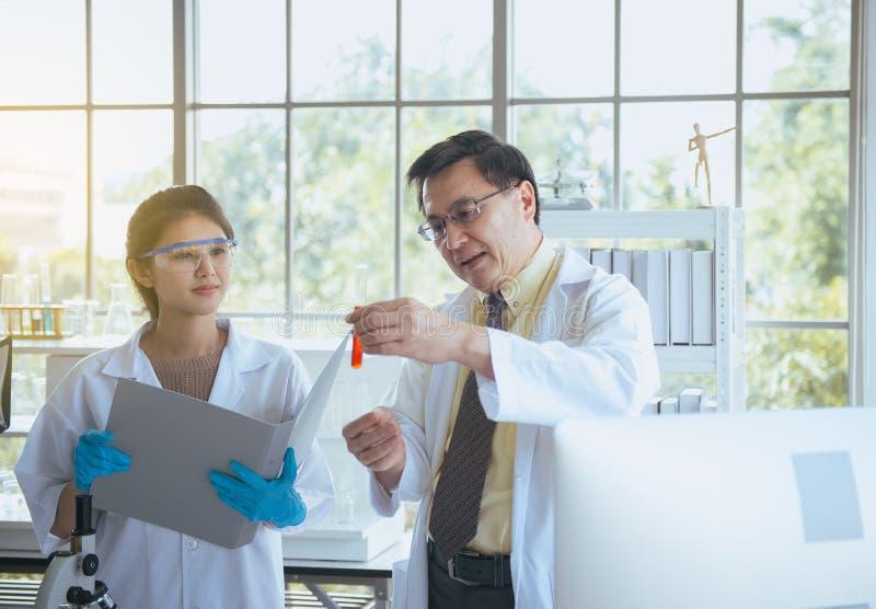 Ανώτερος φοιτητής Ιατρικής διδασκαλίας καθηγητή για να αναλύσει τις ερευνητικές πληροφορίες στοιχείων μαζί στο laboratary στοκ φωτογραφία