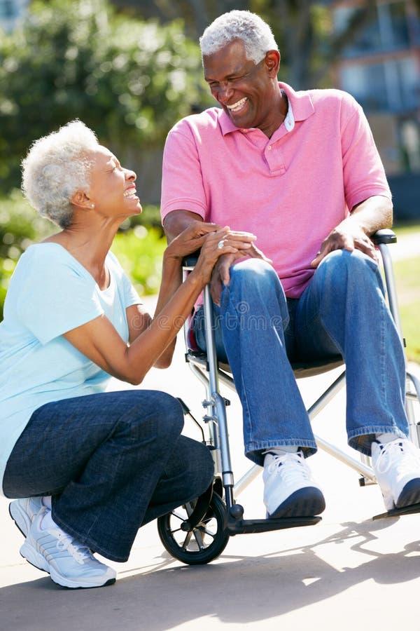 Ανώτερος ωθώντας σύζυγος γυναικών στην αναπηρική καρέκλα στοκ φωτογραφίες με δικαίωμα ελεύθερης χρήσης