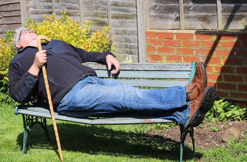 Ανώτερος ύπνος ατόμων στον πάγκο πάρκων στοκ φωτογραφία με δικαίωμα ελεύθερης χρήσης