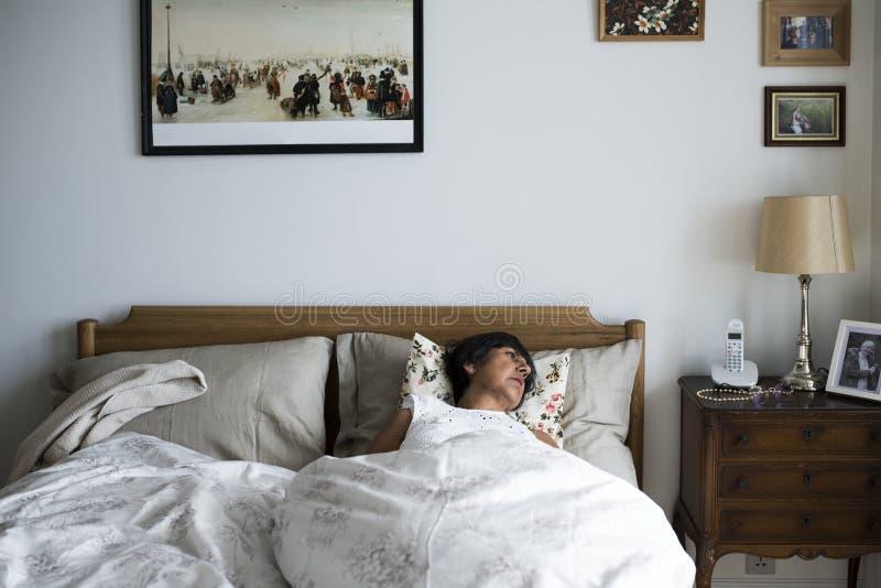 Ανώτερος ύπνος γυναικών μόνο στο κρεβάτι στοκ εικόνες