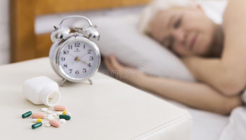 Ανώτερος ύπνος γυναικών στο κρεβάτι με τη βοήθεια των χαπιών στοκ φωτογραφίες με δικαίωμα ελεύθερης χρήσης