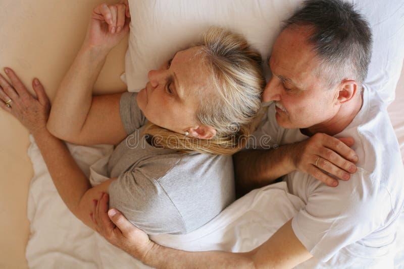 Ανώτερος ύπνος ζευγών μαζί στο κρεβάτι στοκ εικόνες