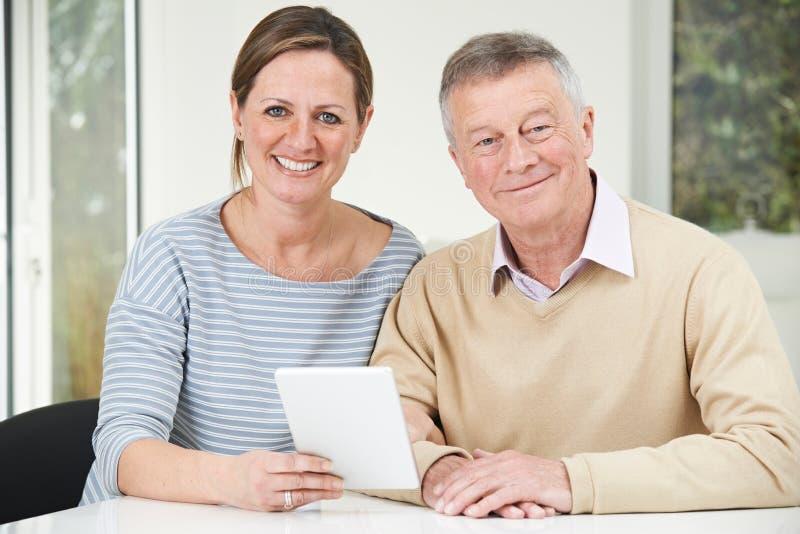 Ανώτερο άτομο και ενήλικη κόρη που εξετάζουν την ψηφιακή ταμπλέτα από κοινού στοκ φωτογραφία