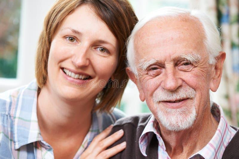 Ανώτερο άτομο με την ενήλικη κόρη στο σπίτι στοκ φωτογραφίες