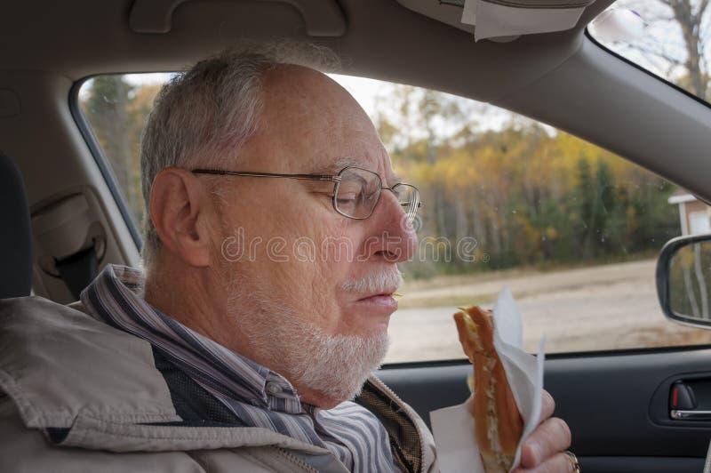 Ανώτερο άτομο με το εκφραστικό πρόσωπο που τρώει τα γρήγορα τρόφιμα στοκ φωτογραφία