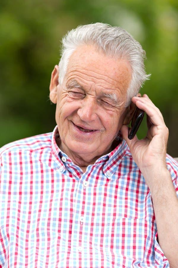 Ανώτερο άτομο με το τηλέφωνο κυττάρων στοκ φωτογραφίες