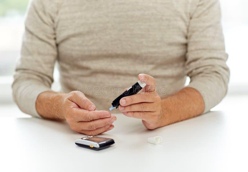 Ανώτερο άτομο με το glucometer που ελέγχει τη ζάχαρη αίματος στοκ φωτογραφία με δικαίωμα ελεύθερης χρήσης