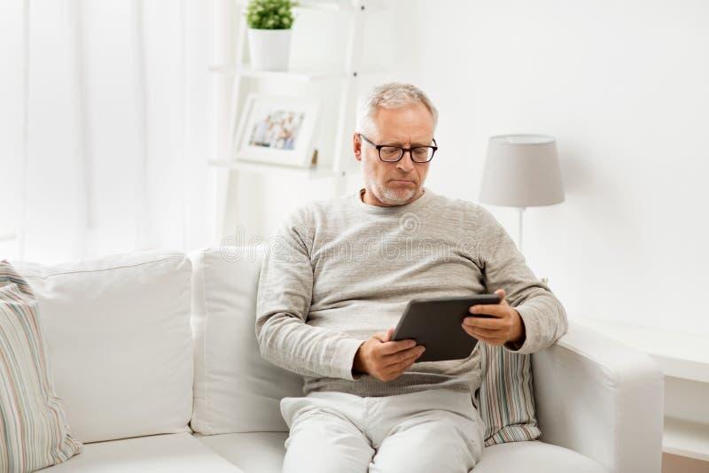 Ανώτερο άτομο με το PC ταμπλετών στο σπίτι στοκ φωτογραφία
