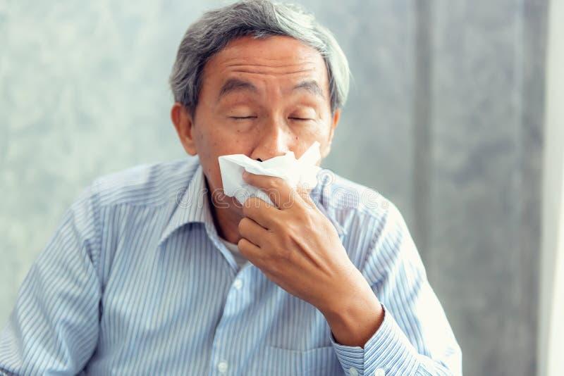 Ανώτερο άτομο που έχει την ασθένεια και που φτερνίζεται στον ιστό, υγειονομική περίθαλψη στοκ φωτογραφίες
