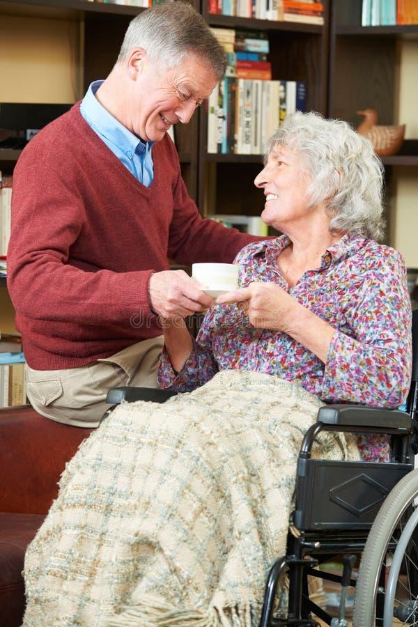 Ανώτερο άτομο που δίνει τη σύζυγο στην αναπηρική καρέκλα φλυτζάνι του τσαγιού στοκ εικόνα με δικαίωμα ελεύθερης χρήσης