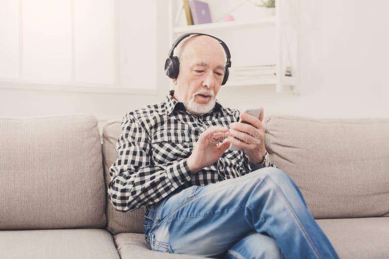 Ανώτερο άτομο που ακούει τη μουσική με τα ακουστικά στοκ εικόνα