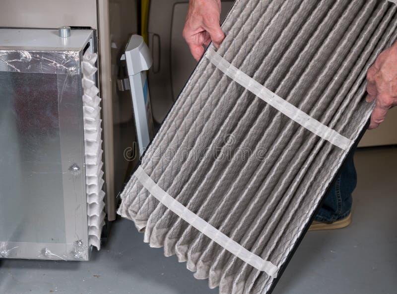 Ανώτερο άτομο που αλλάζει ένα βρώμικο φίλτρο αέρα σε έναν φούρνο HVAC στοκ φωτογραφία