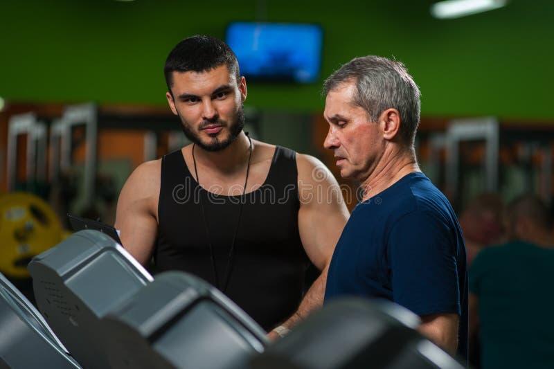 Ανώτερο άτομο που ασκεί η μηχανή στη γυμναστική στοκ εικόνες