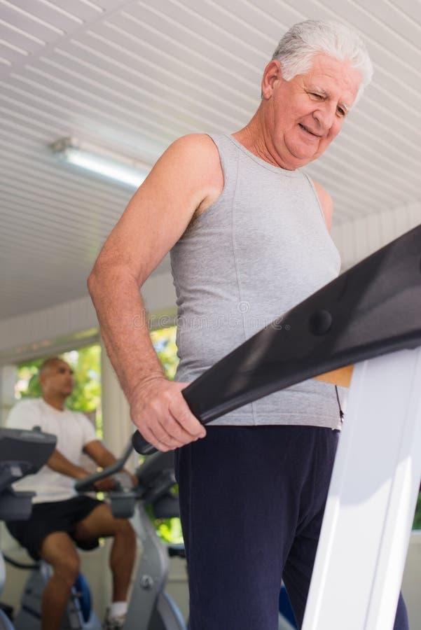 Ανώτερο άτομο που ασκεί στη λέσχη wellness στοκ εικόνες