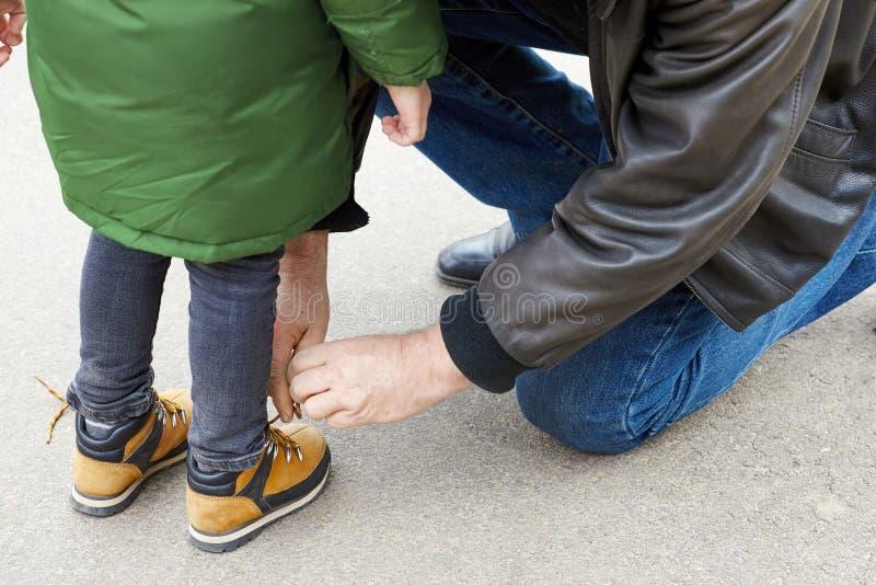 Ανώτερο άτομο που δένει τις δαντέλλες στις μπότες παιδιών Ο πατέρας ή ο παππούς βοηθά το μικρό γιο ή τον εγγονό του Η και η δύο φ στοκ φωτογραφίες