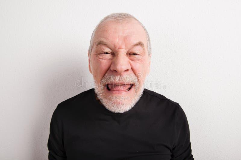 Ανώτερο άτομο που κάνει το αστείο πρόσωπο, πυροβολισμός στούντιο στοκ φωτογραφία με δικαίωμα ελεύθερης χρήσης