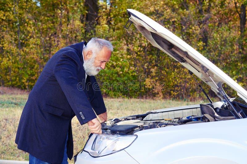 Ανώτερο άτομο που κοιτάζει κάτω από την κουκούλα του αυτοκινήτου διακοπής στοκ φωτογραφίες