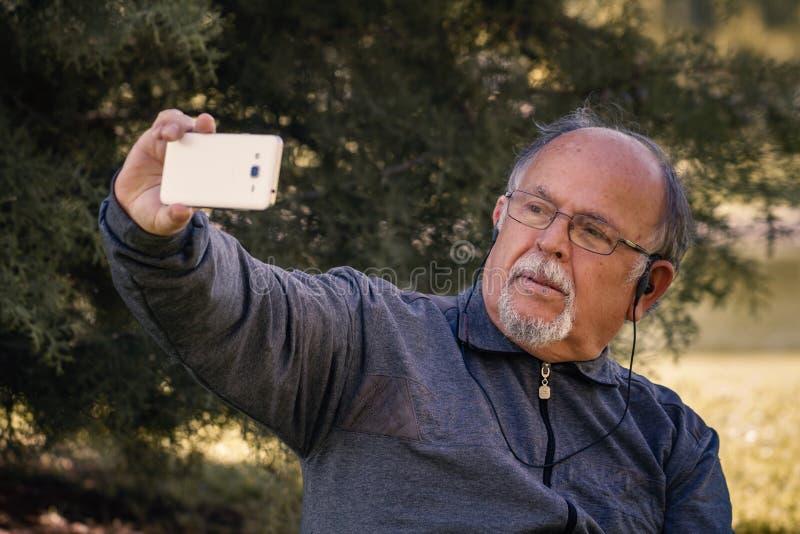 Ανώτερο άτομο που παίρνει ένα Selfie με το έξυπνο τηλέφωνο κυττάρων σε ένα πάρκο στοκ εικόνες με δικαίωμα ελεύθερης χρήσης