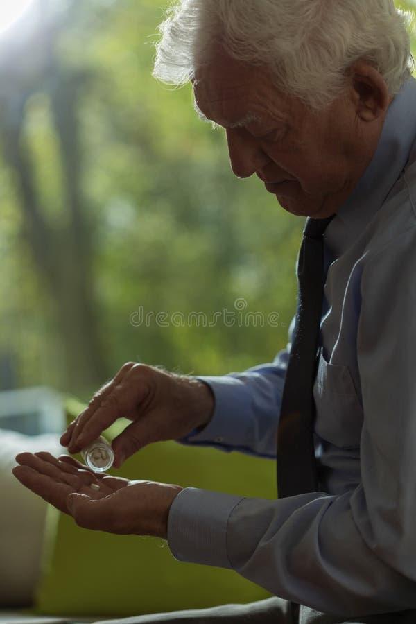 Ανώτερο άτομο που παίρνει τα χάπια στοκ εικόνα