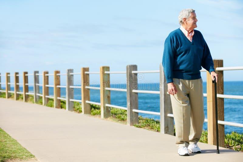 Ανώτερο άτομο που περπατά κατά μήκος του μονοπατιού θαλασσίως στοκ φωτογραφία με δικαίωμα ελεύθερης χρήσης