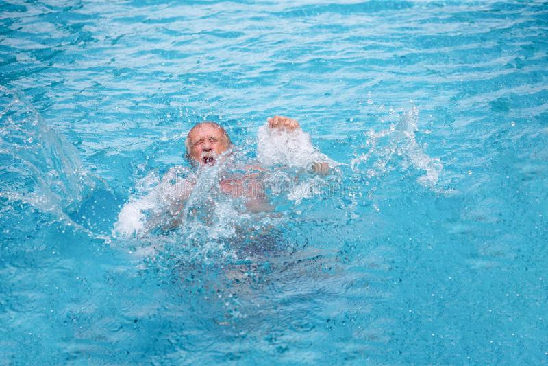 Ανώτερο άτομο που πνίγει στην πισίνα στοκ φωτογραφία