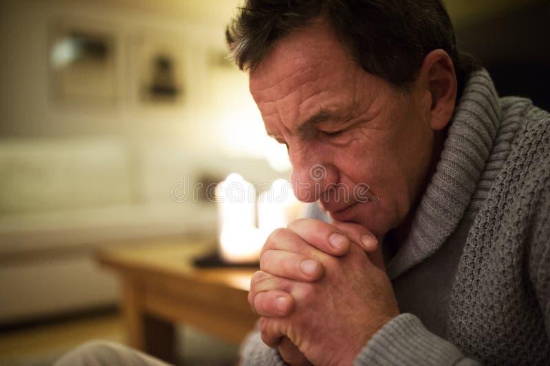 Ανώτερο άτομο που προσεύχεται στο σπίτι, καίγοντας κεριά πίσω από τον στοκ εικόνα