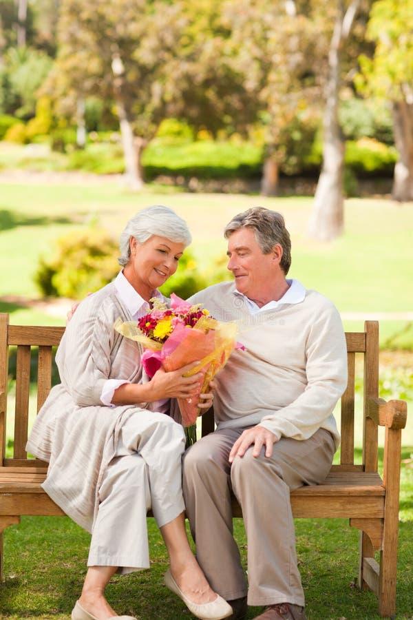 Ανώτερο άτομο που προσφέρει τα λουλούδια στη σύζυγό του στοκ εικόνα