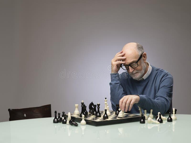 Ανώτερο άτομο που σκέφτεται πέρα από το σκάκι στοκ εικόνα με δικαίωμα ελεύθερης χρήσης