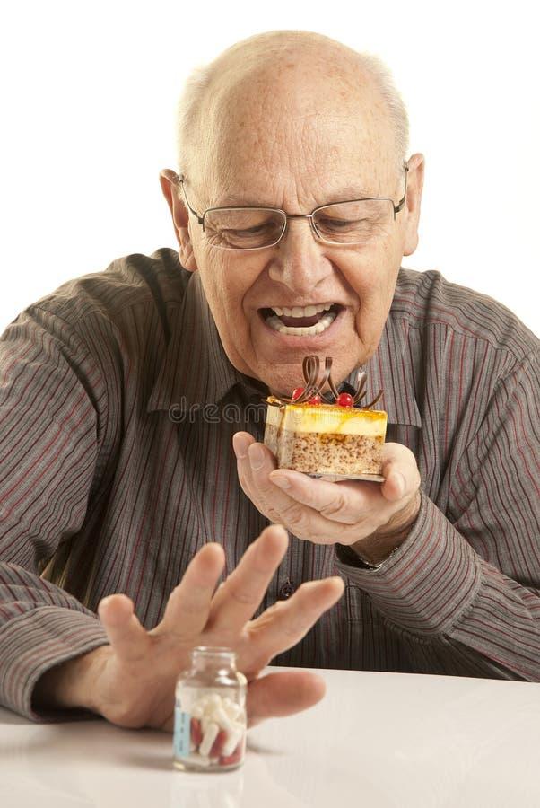 Ανώτερο άτομο που τρώει ένα κέικ στοκ εικόνες